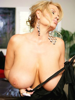 Kellys wearing a clingy black dress orally services a huge cock.